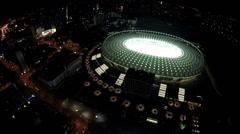 Oval-shaped illuminated football stadium, aerial view on beautiful night city Stock Footage