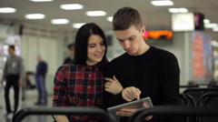 Handsome couple of people sits in departure lounge in airport Stock Footage