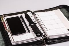 Plan for murderer - calendar, planner, cellphone, pen and knife as weapon Stock Photos
