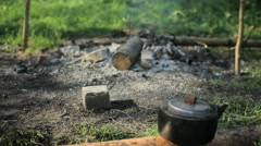 Phone put on a stone near the smoking fire. In the foreground, camp kettle Stock Footage