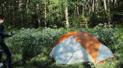 Man photographs on your phone via selfie stick. Nearby stands a tent in the Stock Footage
