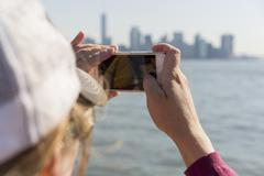Female taking pictures of city with smart phone Stock Photos
