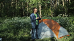 Man making selfie on the phone. Nearby stands a tent in the forest, early Stock Footage