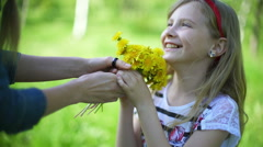 Little girl with mother sitting in the meadow blowing dandelion Stock Footage