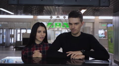 Pair of people answers questions standing on customs control in airport Stock Footage