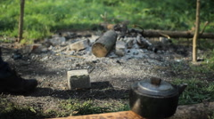 Tablet put on a stone near the smoking fire. In the foreground, camp kettle Stock Footage