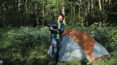 Man making selfie on the tablet. Nearby stands a tent in the forest, early Stock Footage