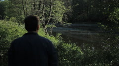 A man walks along the lake and stopped to breathe and look at the water. Early Stock Footage