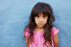 Innocent little girl standing against blue wall - stock photo