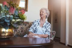 Senior woman sitting on a sofa at old age home - stock photo