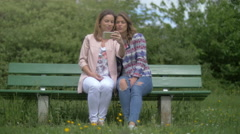 Two young women sitting on a park bench take a selfie Stock Footage