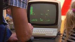 Instructor Teaches Kids to Play Old Computer Game by Joystick Black and Green Stock Footage
