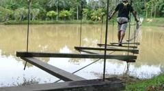 Man walking on the swing bridge Stock Footage
