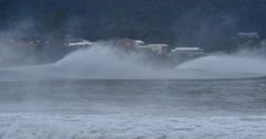 Sea spray form massive waves that are braking along coastal town   Stock Footage