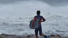 NSW, AUSTRALIA - JUNE 2016: bodyboarder running to surfer big waves Stock Footage