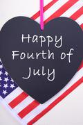 Happy Fourth of July blackboard and flag. - stock photo