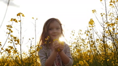 Little girl picking flowers and throws up petals Stock Footage