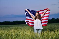 Smiling happy girl with developing the American flag. 4th july - Independence - stock photo