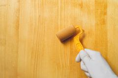 Hand with paint roller applying acrylic lacquer on wooden board Stock Photos
