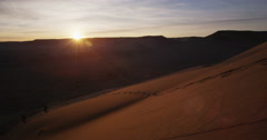 Sun setting behind red sand dune in slow motion Stock Footage