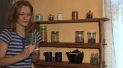 Grower woman smell mint herbs in jar and smile. Static shot. 4K - stock footage