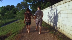 Steady-cam shot young couple walking at sunset Stock Footage