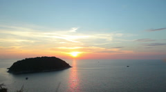A tropical island in the sea at sunset. Red sun sets over the horizon Stock Footage
