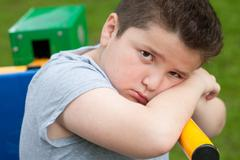 Tired sad fat boy sitting on a fitness equipment Stock Photos
