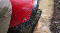 ATV drive through mud puddle Stock Footage