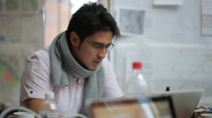 Male of Asian appearance cartographer in glasses and scarf working on the laptop Stock Footage