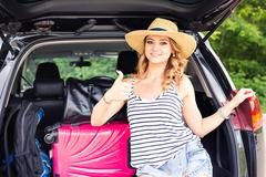 Travel, tourism - woman sitting in the trunk of a car with suitcases, showing Stock Photos