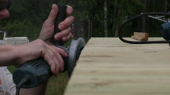 Close up of a man who grinds the wood with an electric sander Stock Footage