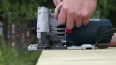 Close up of a man who saws with an electric saw in the wood - stock footage