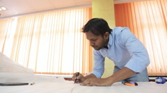 Indian engineer designer drafting draw on a table in a bright room - stock footage