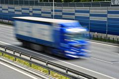 Large goods vehicle moving at full speed on six lane controlled-access highwa Stock Photos