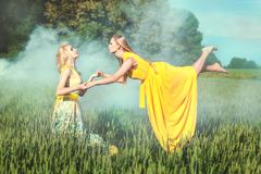Two women hold each other's hands. - stock photo