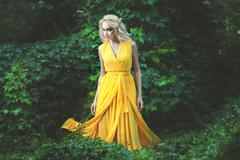 Delightful woman dressed in a yellow dress. - stock photo