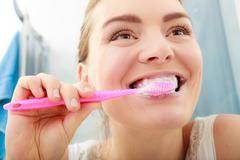 Woman brushing cleaning teeth. Oral hygiene. - stock photo