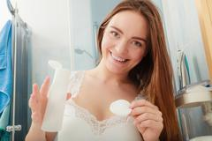 Woman removing makeup with cotton swab pad. Stock Photos