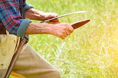 Farmer with beard sharpening his scythe for using to mow the grass traditiona Stock Photos