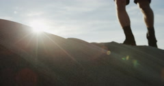 Hiking boots on a sand dune going past sun flare in slow motion Stock Footage