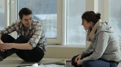 Two friends sit near big window and discuss plan of building Stock Footage