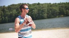 Young Man Throwing Football on Beach at Lake Having Fun Slow Motion Stock Footage