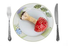Red toadstool on dish with knife and fork. - stock photo