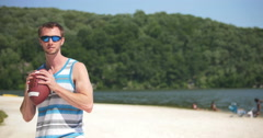 Young Man Throwing Football on Beach at Lake Having Fun, 4K Stock Footage
