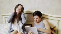 Young pair listening to music on headphones and use the tablet. Arkistovideo