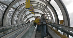 People riding escalators in glass tube Stock Footage