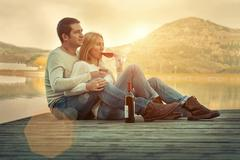 Romantic Couple sitting on the pier with red wine. Stock Photos