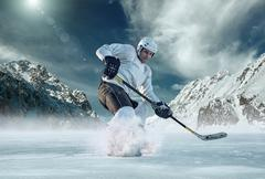 Ice hockey player in action outdoor around mountains Stock Photos