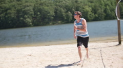 Running to Catch Football on Beach at Lake a Young Man Slow Motion - stock footage